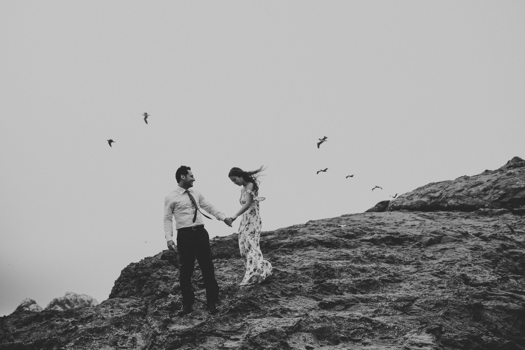 Couple walking in Sutro Bath holding hand with bird flying around them